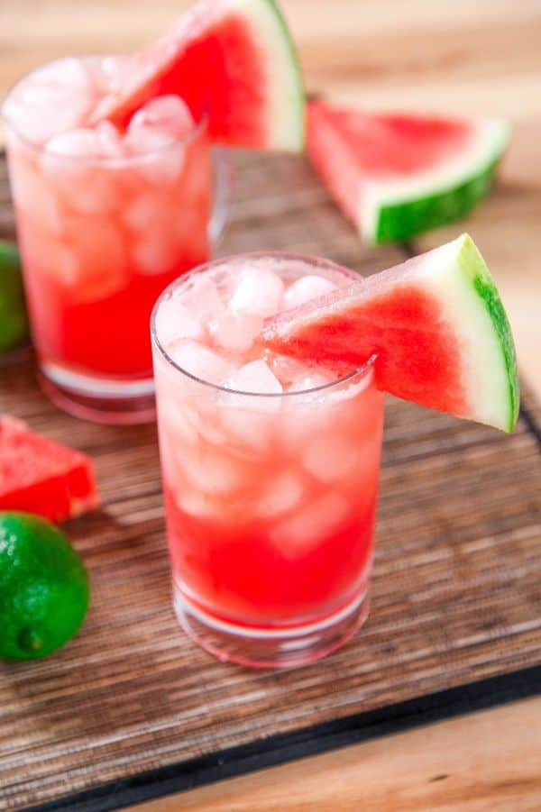 two glasses of sparkling watermelon cocktail with ice topped with watermelon slice on a brown table with more slices of watermelon and a lime in the background