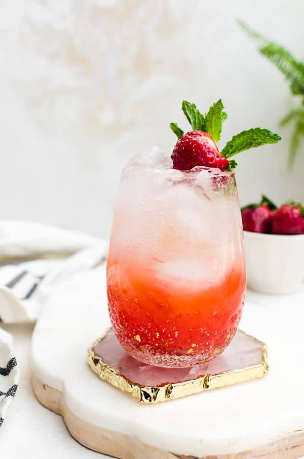 strawberry champagne mojito in a glass with ice topped with a strawberry with more strawberries in the background all on a white slab