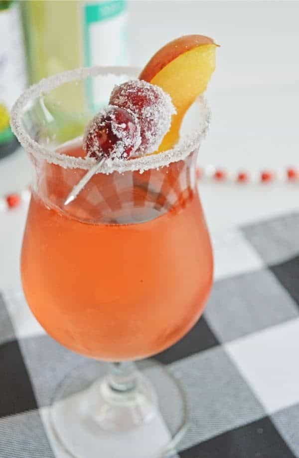 sugar plum fairy cocktail in a glass rimmed with sugar topped with berries and a peach slice on a black and white checkered linen