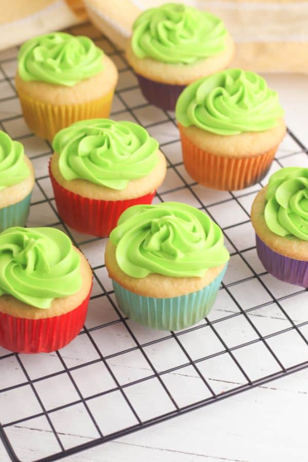 white cupcakes topped with green frosting on a wire rack
