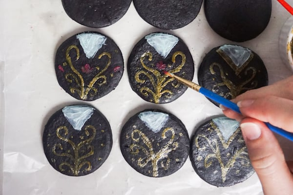 a hand painting white and gold icing with a paintbrush on  black fondant circles