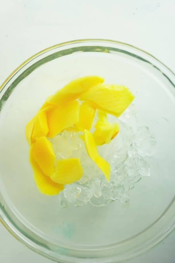 mango pieces and ice in a glass bowl on a white background