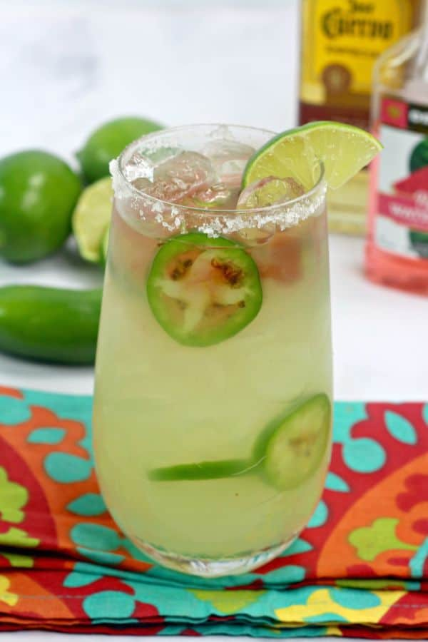 Texas Margarita with sliced jalapenos  in it and a lime wedge in a glass rimmed with salt on a turquoise and orange cloth on a white table with bottles of alcohol, jalapenos, and limes in the background