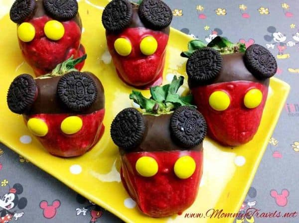 chocolate covered strawberries decorated with yellow candies and mini oreos to look like Mickey Mouse on a yellow plate on a mickey and minnie mouse cloth