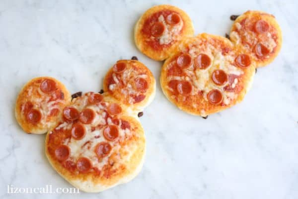 two pepperoni pizzas put together to look like mickey mouse on a white counter