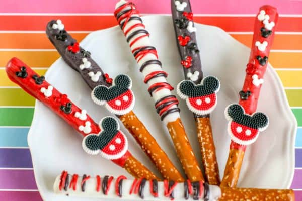 mickey mouse pretzels sticks on a white plate on a rainbow colored background