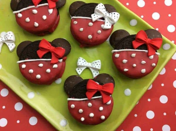 oreo cookies decorated with red and white frosting and a red bow to look like minnie mouse on a green plate on a red and white polka dot paper