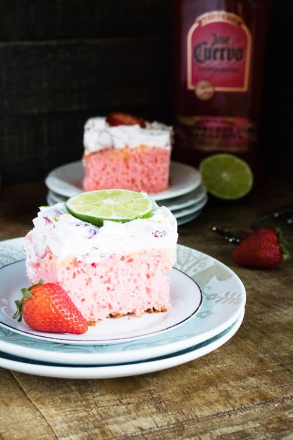 two slices of Strawberry Margarita Poke Cake on two plates on a brown table next to a strawberry, spoon, lime and bottle of alcohol