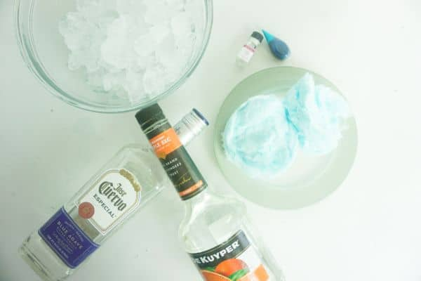 bowls of ice and blue cotton candy, bottles of tequila and triple sec, blue food coloring, and cotton candy food flavoring oil on a white background