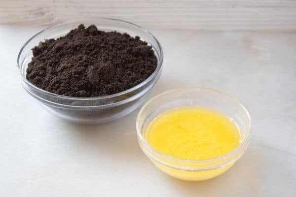crushed oreos and melted butter in glass bowls on a white counter