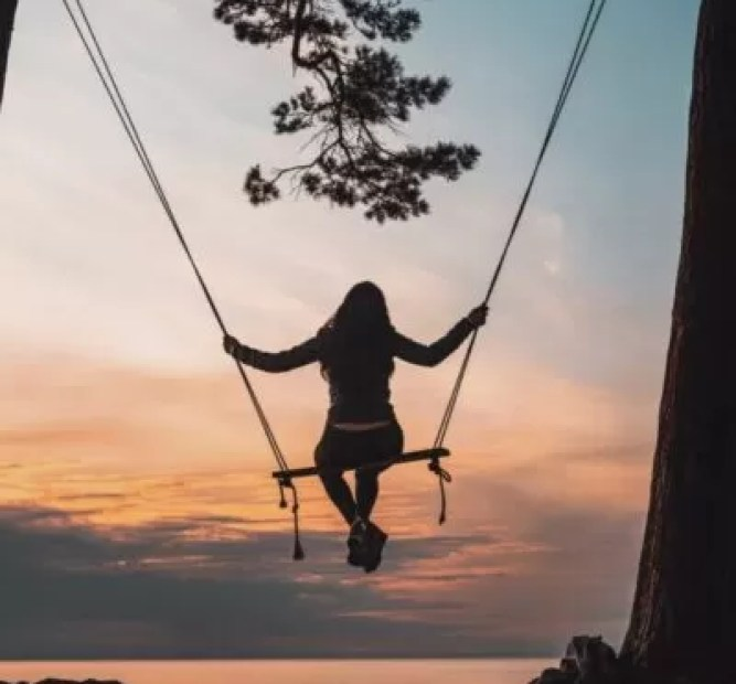 silhouette of person sitting on swing during sunset