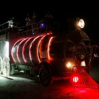 An art car shaped like a train drives across the desert in the early morning hours at the 2013 Burning Man arts and music festival in the Black Rock desert of Nevada