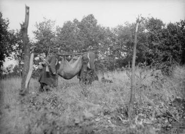 Тешко повређен српски војник на носилима направљеним од шатора.