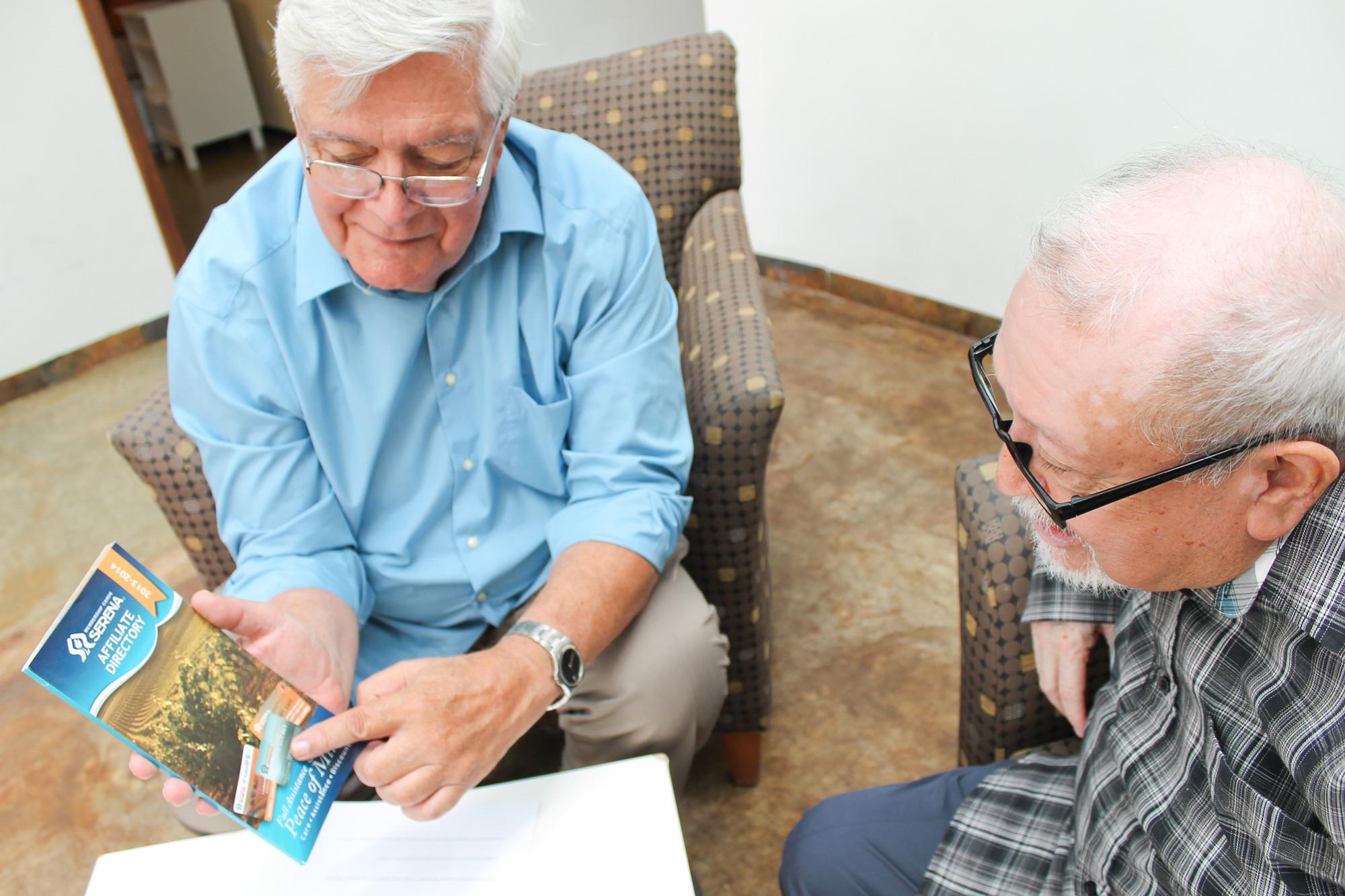 Un feliz tarjeta habiente comparte información sobre Serena a otro adulto mayor