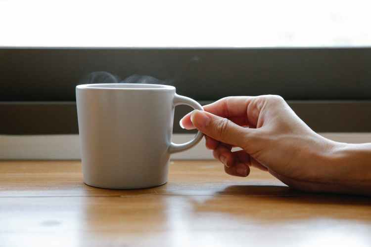 crop faceless woman touching cup of aromatic hot drink
