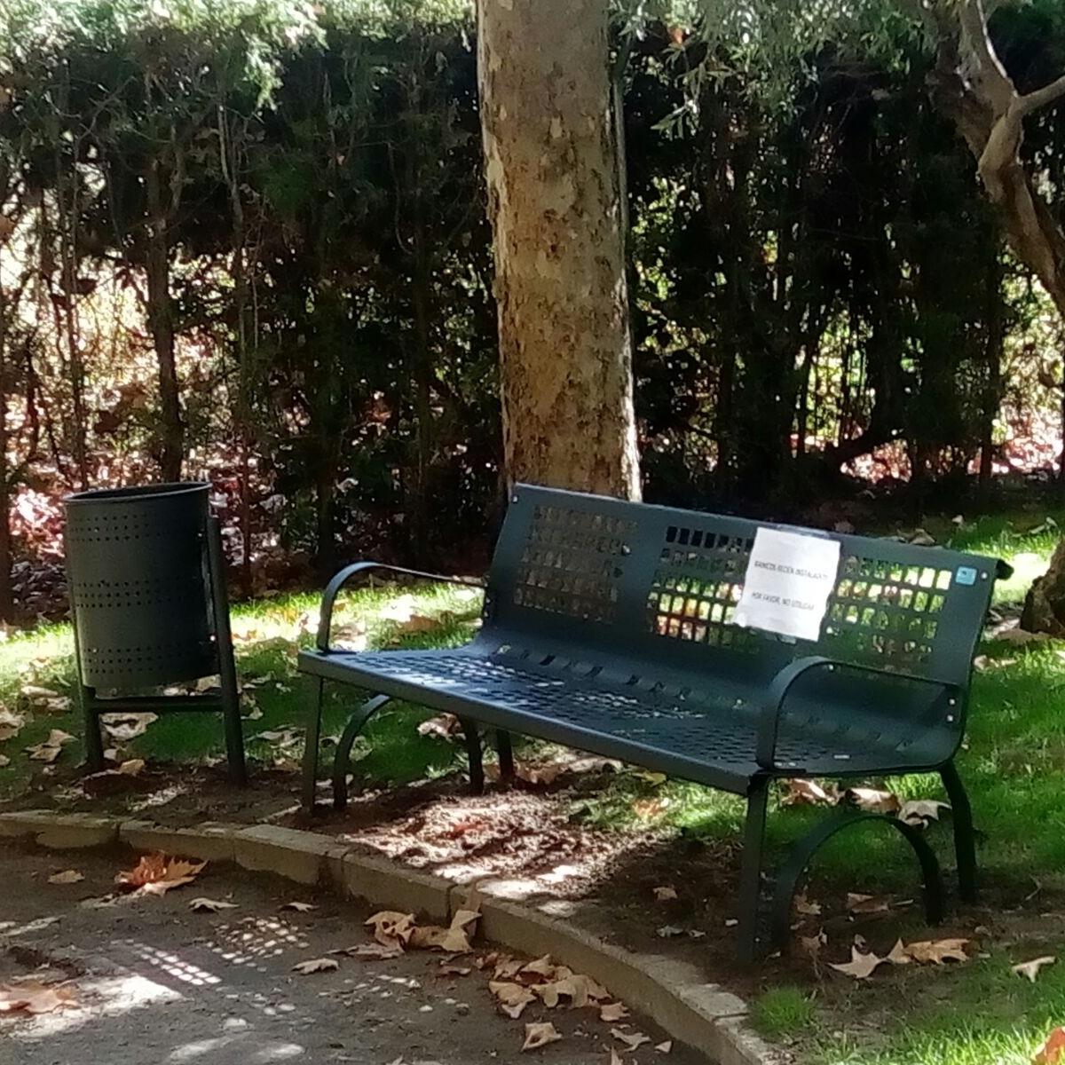 banco urbano de la marca sergin junto a papelera urbana instalado en un jardin