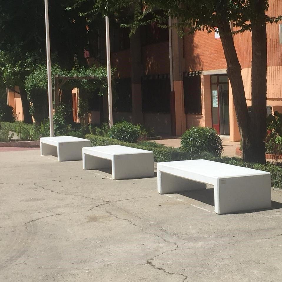 conjunto de bancos prefabricados de la marca sergin en las puertas de centro educativo de madrid