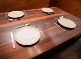 Wooden dinner table set with four place settings with cutlery and empty white ceramic plates