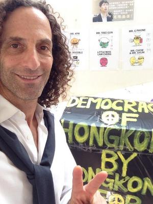 Based on Kenny G's ageless appearance, it's possible that he merely jumped in time from 1993 directly to the 2014 Hong Kong protests. Or he's an elf.