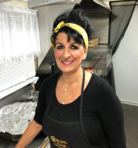 Valerie, the owner of Serrianni's, smiling in the kitchen