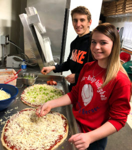Bradley and Isabella, young members of the Serrianni family, smiling and making pizzas