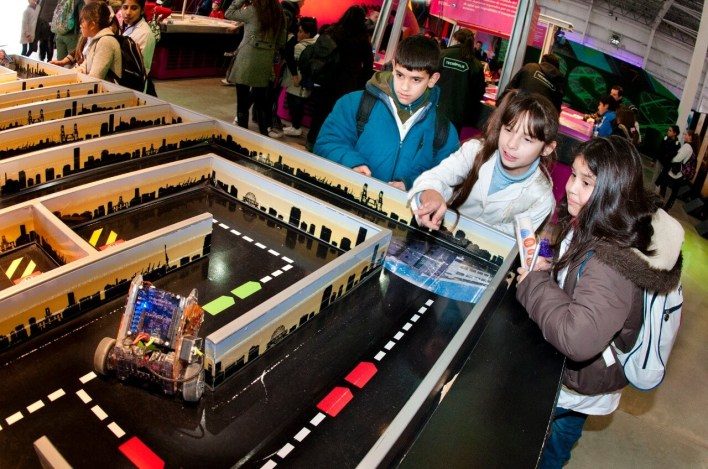 Crianças observando um pequeno robô percorrendo um circuito.