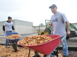 Pastor Scott Miller helps spread bark chips at Sunrise Elementary.