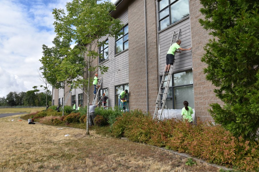 Volunteers working at multiple heights to paint Timber Ridge.
