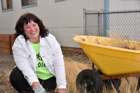 Principal Anna Keifer pulls weeds at Jefferson Elementary.