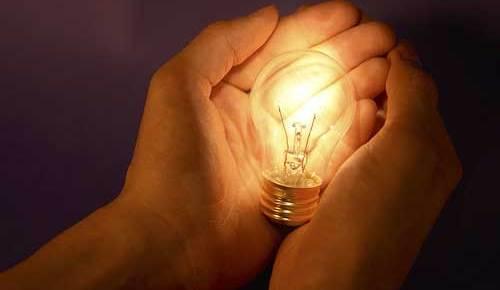 hands holding incandescent light bulb color