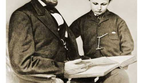 president abraham lincoln seated reading book son tad white house black and white
