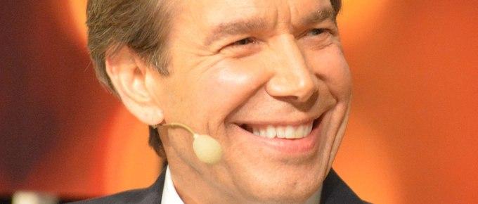 jeff koons color smiling headshot great suit tie microphone orange background