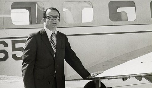 william ruckelshaus standing black and white outside small plane