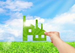 Hand hold factory iconon field and blue sky background, Eco green factory concept