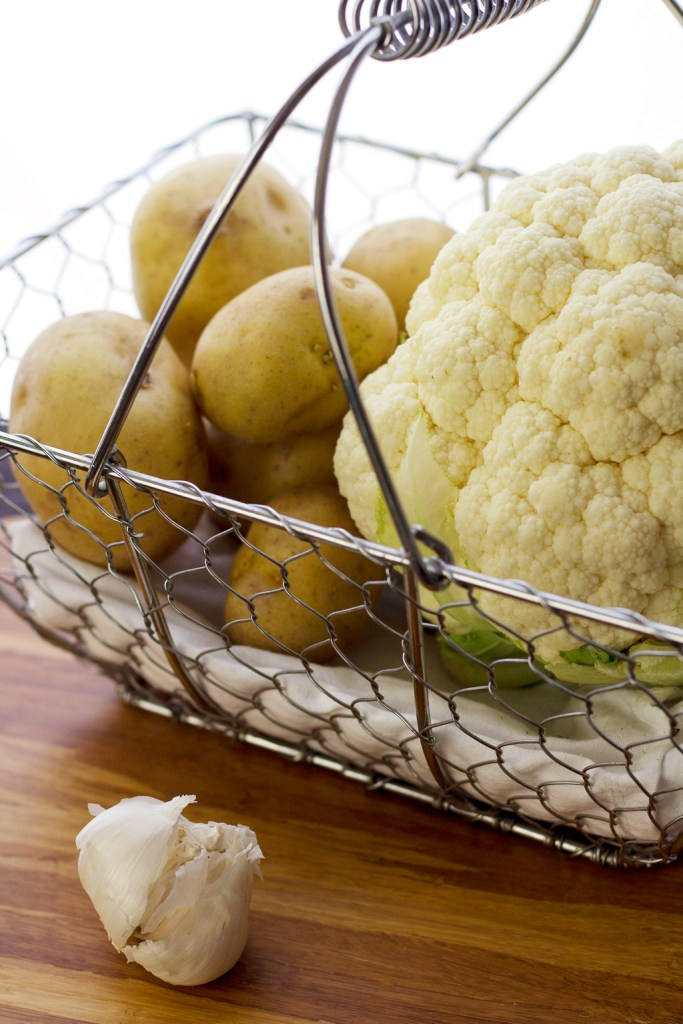 cauliflower and yukon gold potatoes in basket prepping for cauliflower mashed potato recipe