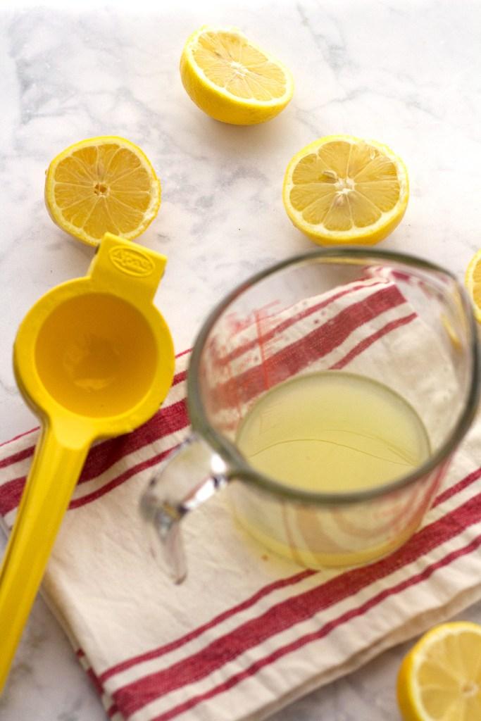 Freshly juiced lemons for easy vegan strawberry ginger lemonade recipe