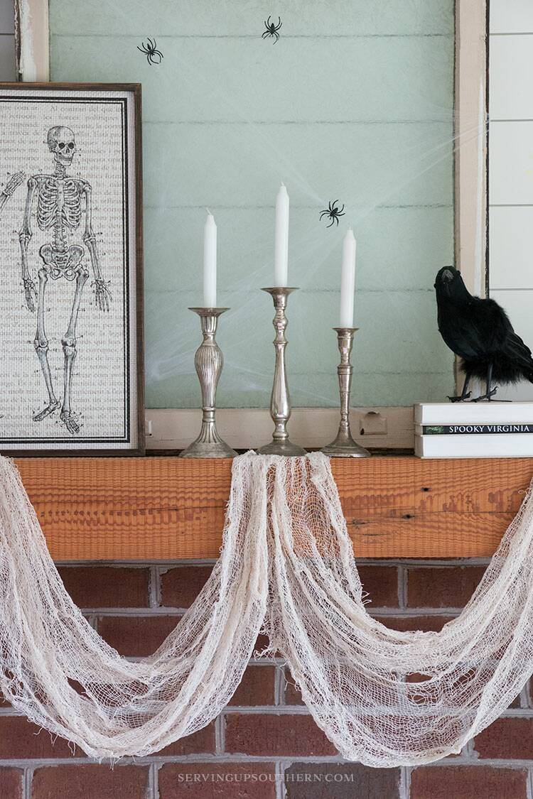 A mantel decorated with black crows, a human skeleton picture, a spider web with spiders, and pumpkins.