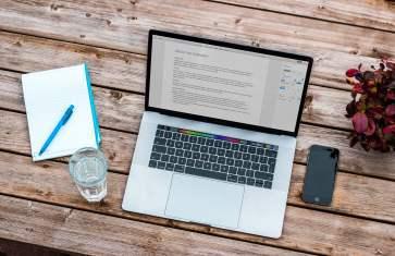 Laptop, text online, caiet, pahar de apa, telefon, flori in vaza pe masa
