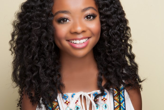 Skai Jackson wearing a white, open-shouldered shirt with mosaic beading details