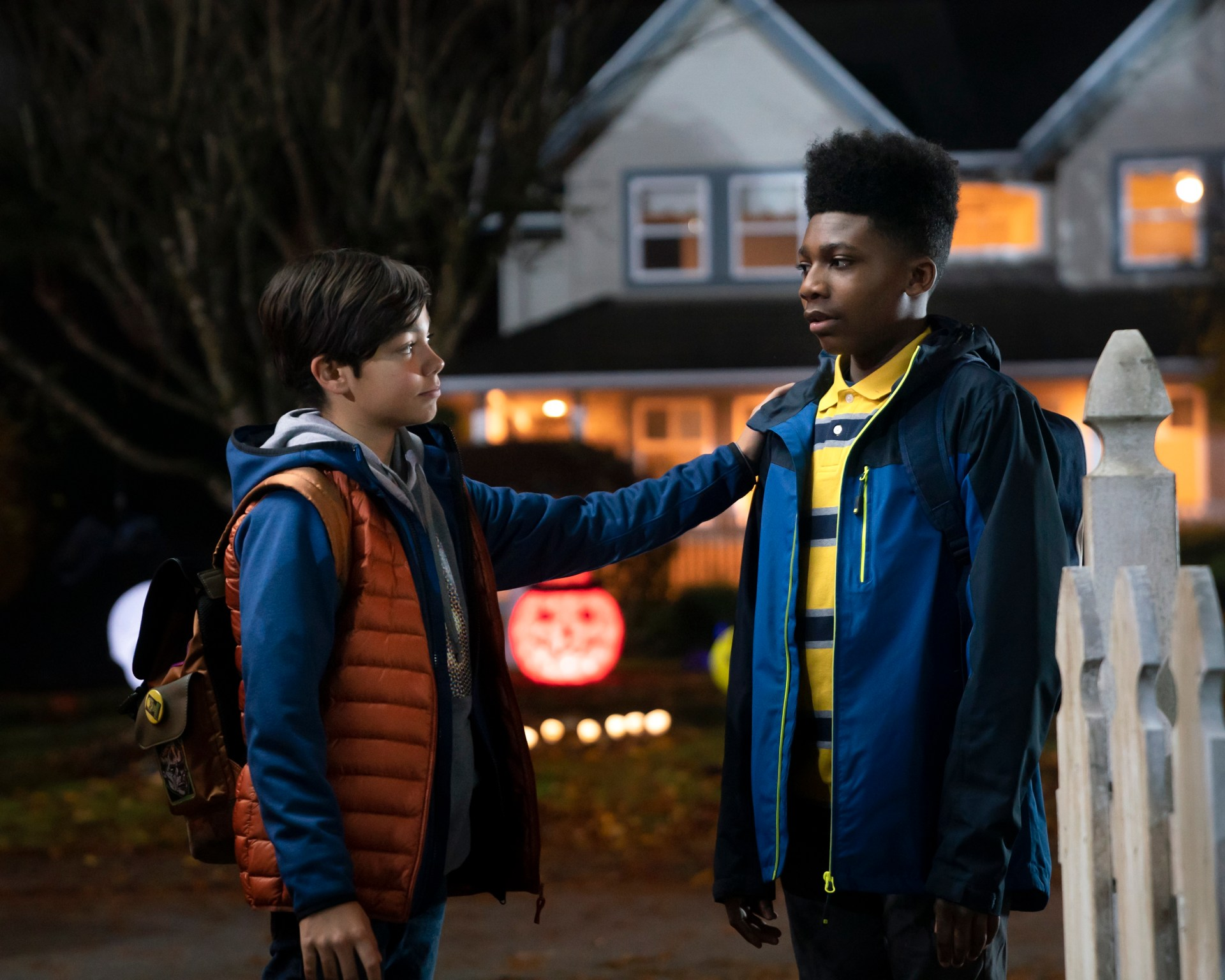 """Christian J Simon, wearing a yellow and blue striped shirt, dark blue jacket, and backpack stands next to co-star Malachi Barton in front of a house decorated for Halloween in this still from """"Under Wraps."""""""