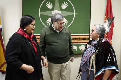 Attorney General William Barr, center, speaks with Myrna DuMontier, left, and Charmel Gillin, councilwomen with the…