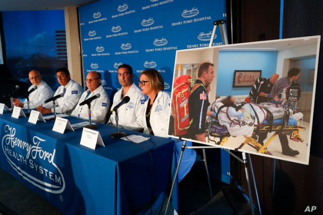 A photo of a patient being transported is displayed while medical staff at Henry Ford Hospital answer questions during a news conference in Detroit, Nov. 12, 2019.