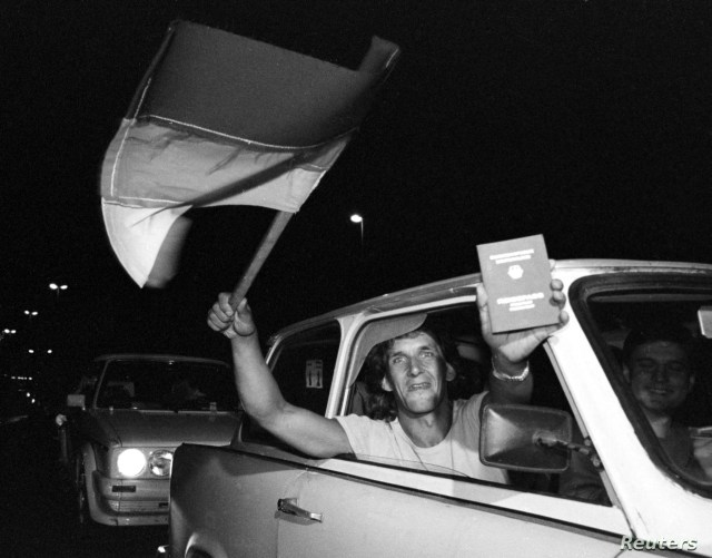 FILE - An East German refugee shows off a newly acquired West German passport just before crossing the Hungarian border into Austria, Sept. 10, 1989.