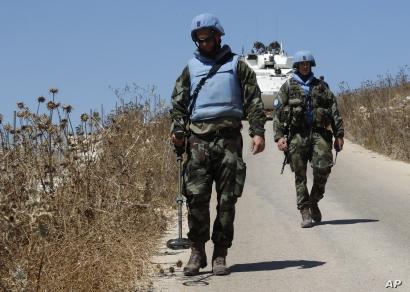 Irish U.N. peacekeepers use mine detectors as they patrol near the fields struck by Israeli army shells in the southern Lebanese-Israeli border village of Maroun el-Ras, Lebanon, Sept. 2, 2019.