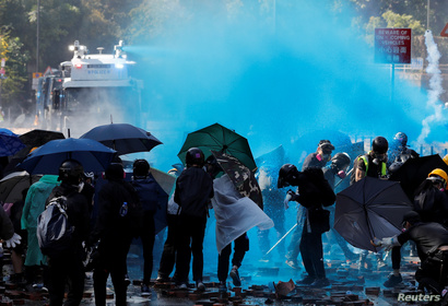 Protesters are sprayed with blue liquid from water cannon during clashes with police outside Hong Kong Polytechnic University …