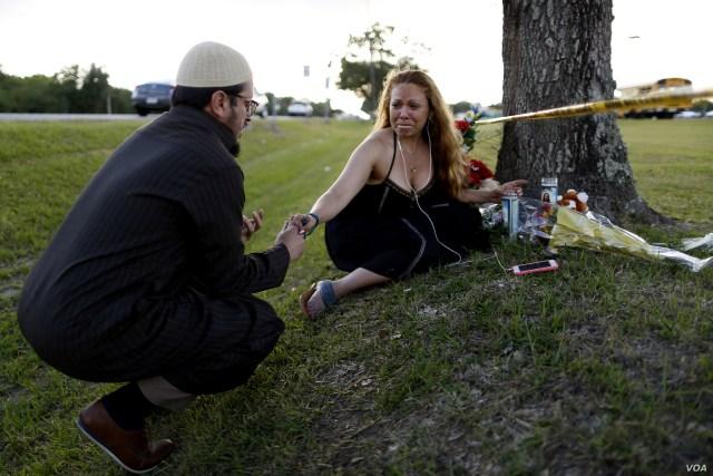 Daniel Hernandez, a local imam, comforts Dih-Anaa Forero of Missouri City, near the site of the shooting at the Santa Fe High School, in Santa Fe, Texas, U.S., May 19, 2018.