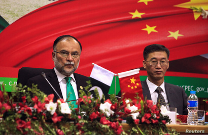 Ahsan Iqbal (L), Pakistan's Minister of Planning and Development and Yao Jing, Chinese Ambassador to Pakistan attend the…