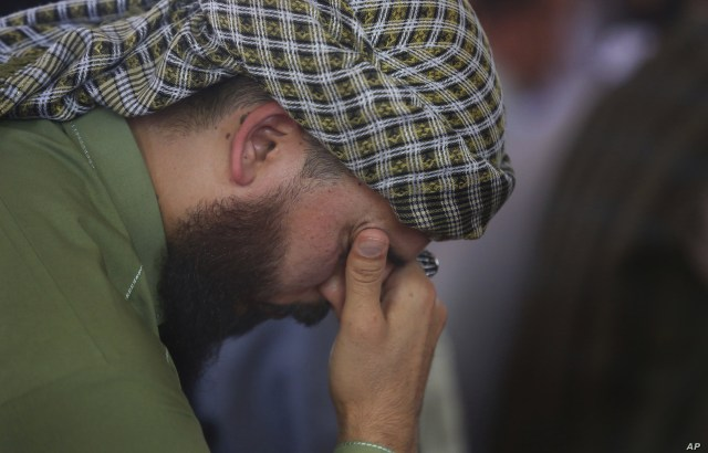 A man mourns for victims of the wedding hall bombing during a memorial service at a mosque in Kabul, Afghanistan,  Aug. 20, 2019.