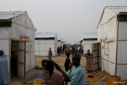 People walk near makeshift accommodation at Bakassi Camp for internally displace people in Maiduguri, Nigeria, March 8, 2016.