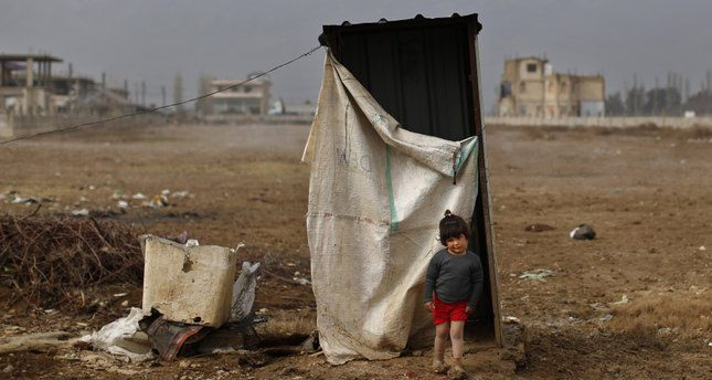 In this picture taken Monday, Jan. 4, 2016, a Syrian refugee girl walks in mud from the heavy rain, as she leaves a restroom at a refugee camp in the town of Hosh Hareem, in the Bekaa valley, east Lebanon. A snowstorm engulfed Lebanon on the first day of the new year, cutting off mountain roads, isolating villages and worsening living conditions for tens of thousands of Syrian refugees. (AP Photo/Hassan Ammar)